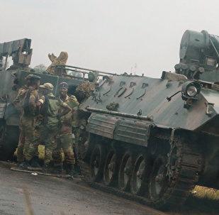 Военнослужащие и бронетехника на подъезде к столице Зимбабве