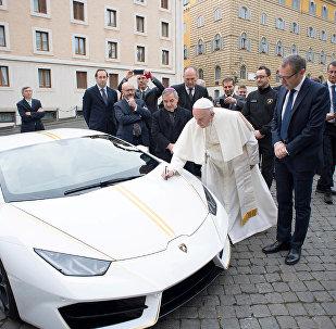 Папа Римский расписывается на капоте Lamborghini Huracan
